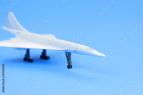 Toy airplane on plain blue background