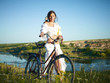 young woman with a bicycle on the nature