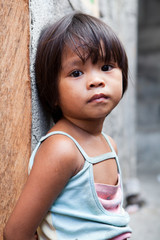 Philippines - young girl in poverty against wall