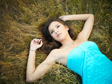 Beautiful young woman lying in the grass