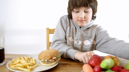 Young boy choosing fast food instead of vegetables and fruits