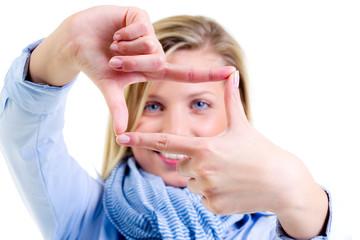 junge frau schaut durch einen fingerrahmen