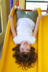 upside down little girl on playground slide laughing