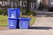 Three small recycle bins on curb