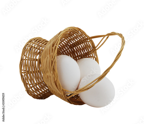 three white eggs spilled from straw interwoven basket