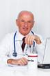Arzt in Arztpraxis mit Stethoskop und Laptop.