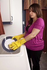 Young Pregnant Woman washing dishes