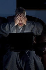 Man in housecoat working late series shocked computer crash