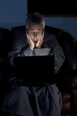 Man in housecoat working late series surprised