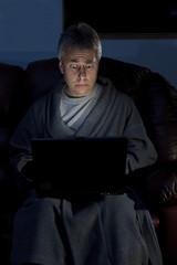Man in housecoat working late series worried