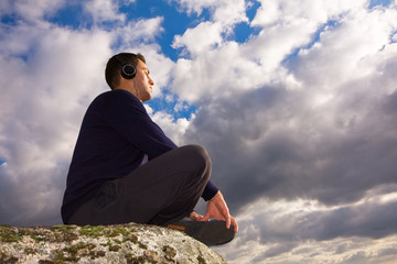Young man listening music in the top of a mountain