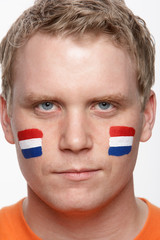 Young Male Sports Fan With Dutch Flag Painted On Face