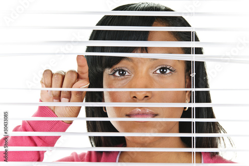 Woman looking through venetian blinds