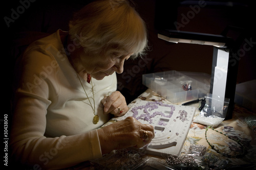 Senior woman making a necklace