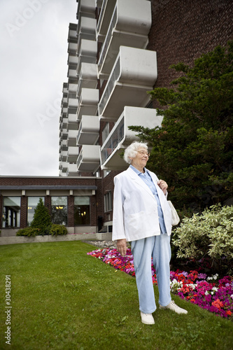 Senior woman in front of apartment building