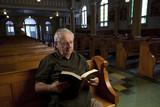 Senior man reading a bible in church poster