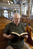Senior man reading a bible in church poster