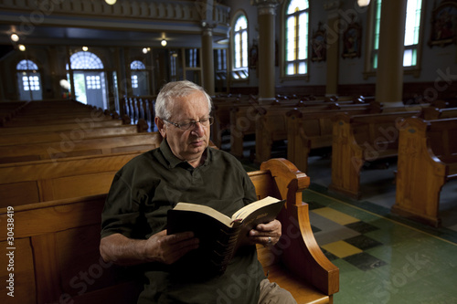Senior man reading a bible in church