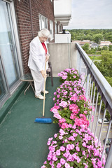 Senior woman brooming her balcony