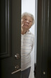 Annoyed senior woman answering front door