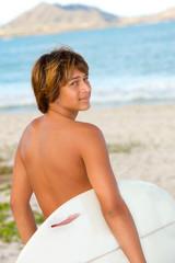 Surfer boy looks over his shoulder
