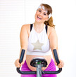 Happy pregnant woman working out on static bike at home.