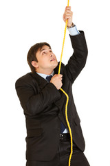 Stubborn young businessman climbing up on rope