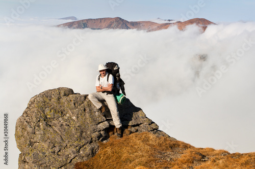 A man with a backpack sitting on the edge of a cliff in the moun