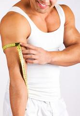 Young man measuring his biceps
