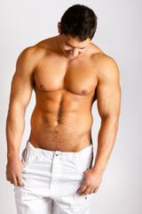 Fashion portrait of sexy male fitness model against neutral back