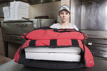 Waitress with take out pizza boxes in a thermal bag
