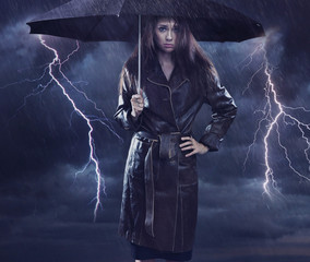 Single woman wearing coat holding umbrella. Creative szmbol of t