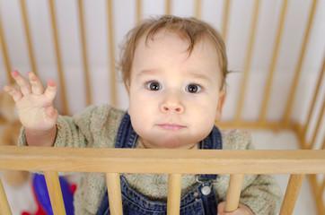 Baby winkt im Laufgitter