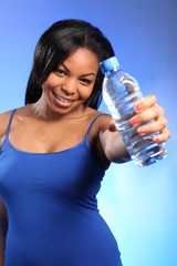 Happy young black girl holding out bottled water