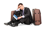 Sad business traveler seated next to a suitcase with a ticket poster