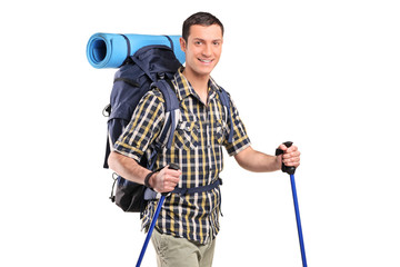 A happy hiker with hiking poles and backpack posing