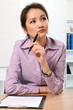 Thoughtful Asian business woman working in office
