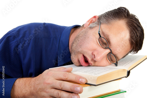male nerdy geek fall asleep with face on pile of books