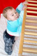 Baby zieht sich am Laufgitter hoch