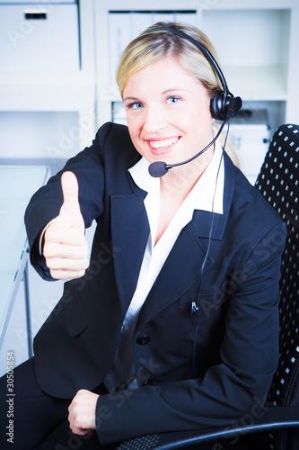 blonde frau mit headset zeigt daumen hoch