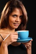 Young woman with a refreshing cup of tea on black background