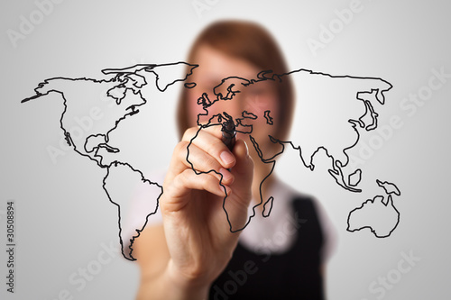 businesswoman drawing the world map in a whiteboard
