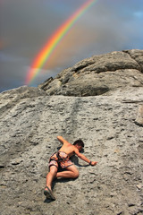 A rock climber on a cliff on the background of the rainbow