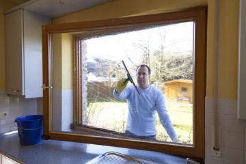Mann beim Fenster putzen