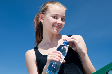 Yyoung woman drinking water after exercise