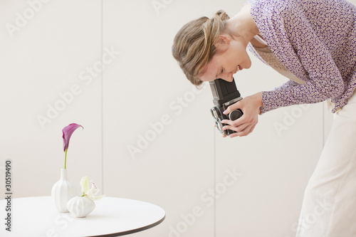 Woman photographing flowers in vases with retro camera