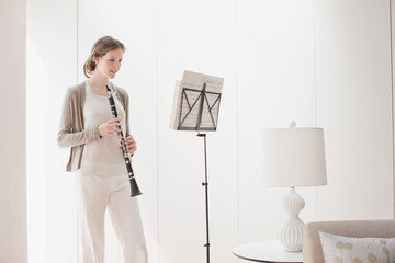 Woman holding clarinet and looking at sheet music