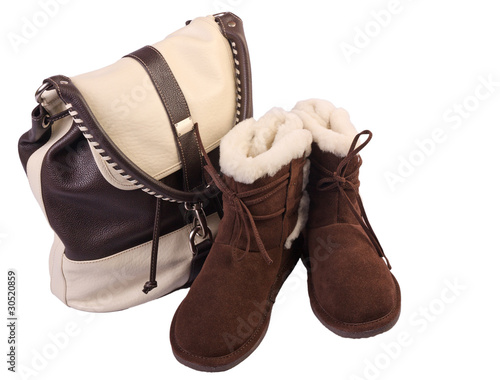 Fluffy woolly warm boots and leather handbag over white backgrou