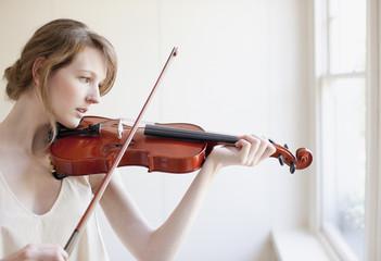 Woman playing violin near window