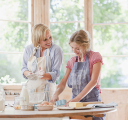Mother and daughter baking at table in kitchen